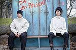 Zwei Schauspielerinnen mit weißen Pullovern sitzen vor einem Spind in einem Park.