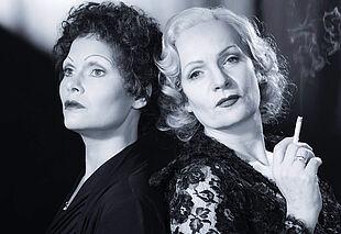 Zwei Frauen Rücken an Rücken in schwarz-weiß.
