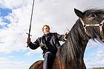 Ein Schauspieler mit einem Schwert in der Hand sitzt auf einem schwarzen Pferd.