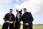 Zwei Schauspieler in schwarzer Kleidung stehen mit einem schwarten Pony auf einer Koppel.