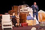 Eva Kewer als Sabeth sitzt in einem Sessel und hält ein Bild hoch, Marko Gebbert als Faber steht und erzählt mit erhobenem Zeigefinger.