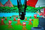 Mengqi Zhang als Mowgli in einem Netz hängend, vor Comichintergrund, der viele kleine rote Affen zeigt