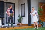 Zacharias Preen als Lionel steht auf der Terrasse und spricht mit Isabel Baumert als Celia, die auf dem Rasen steht.