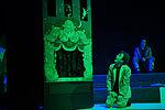 Simon Burghart als Pinocchio im Dunkeln neben einem Puppentheater kniend