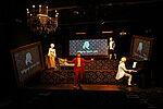 Ein Schauspieler präsentiert im Anzug die Szene in einem Museum, rechts im Bild ein Mann im barocken Kostüm am Klavier. Schaus