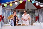 Zacharias Preen als Lionel und Isabel Baumert als Celia stehen in einem Partyzelt und blicken auf ein Brot.