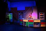 Eine Frau (Elisabeth Frank) schlägt mit Löffeln auf verschiednene Töpfe und Küchenutensilien