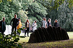 Eine Gruppe von Menschen mit Kopfhörern steht vor einem Gedenkstein