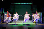 Tony Marossek als Hahn und drei Schauspielerinnen als Hennen verkleidet tanzen, sie halten ein Seil in den Händen.