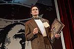 Mann im Anzug hält eine Gesamtausgabe von Shakespeare unterm Arm