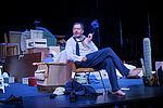 Marko Gebbert als Faber sitzt auf einem Stuhl und raucht.