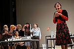 Eine Sekretärin singt im Vordergrund, viele Sekretärinnen stehen im Hintergrund