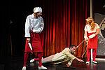 Mann in Kochkostüm mit einem Messer in der Hand, Küchenhilfe führt einen Mann mit einem Strick um den Hals