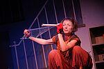 Eine Frau (Elisabeth Frank) schaut durch eine Frischhaltefolienrolle und zieht welche von ihr ab
