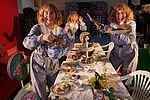 Drei Schauspielerinnen laden mit großen Gesten an eine reich gefüllte Tafel ein.