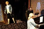 Ein Mädchen in Alltagskleidung beugt sich zum Mann am Klavier