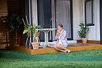 Isabel Baumert als Celia sitzt auf dem Boden einer Terrasse und raucht.