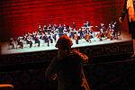 Der Mann vom Klavier dirigiert ein Orchester, das im Museum in einer Vitrine steht.