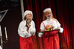 2 Männer in Küchenkostümen mit einer Servierplatte in der Hand