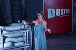 Eine Frau lehnt mit auffälligem Make-Up, in einem hellblaueb Kleid an Lüftungsrohren