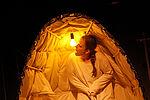 Patricia Windhab als Gregor Samsa in einem weißen Kokon sitzend, eine Glühbirne leuchtet in dem Kokon