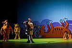 Maria Gulik als der schwarze Panther Bagheera, Kammersänger Jörg Sabrowski als Shere Khan auf dem Comichintergrund ist ein gegrillter Büffel zu sehen