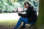 Eine Frau mit Kopfhörern sitzt an einem Baumstamm und schaut auf ihr Handy